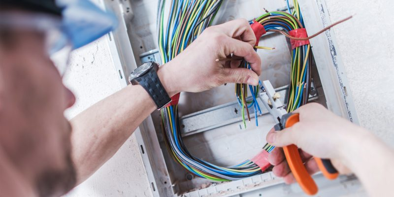 Electrical System Installation by Professional Caucasian Electrician. Construction and Power Industry Theme.