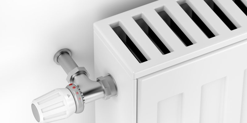 Close-up of white heating radiator with thermostat valve